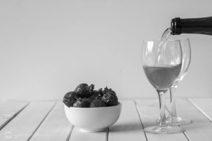 Pouring Wine in Glasses and a Bowl of Strawberries on a White Wooden Table with Copy Space