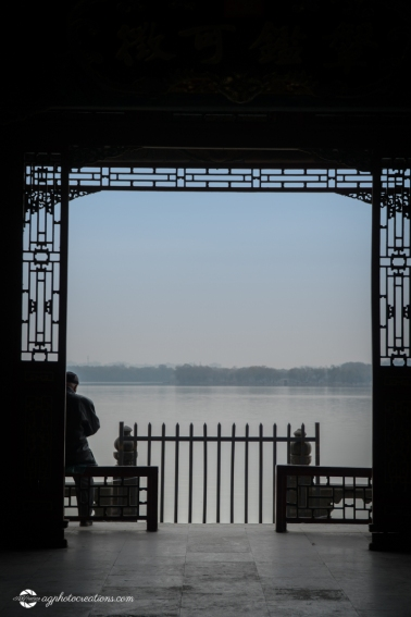 Unidentified Chinese Man Sitting in Archway by the Lake At the Summer Palace in Winter, Beijing China