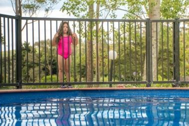 Pool Safety - Young Girl Standing Outside Pool Fence Looking In To Pool Northland New Zealand